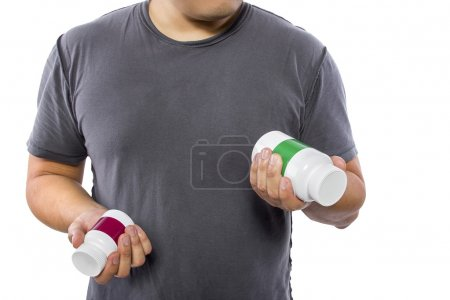 Man comparing bottles of medicine