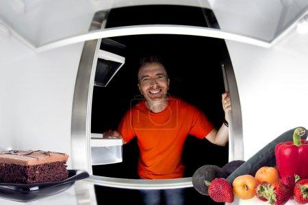 Man looking inside fridge