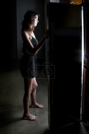 Woman  looking for food in  frige