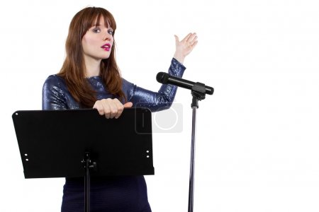 Caucasian girl speaking into a microphone and gest...