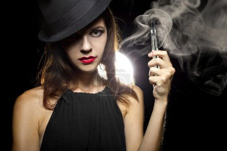 Photo pour Woman vaping an electronic cigarette to quit tobacco on black background - image libre de droit