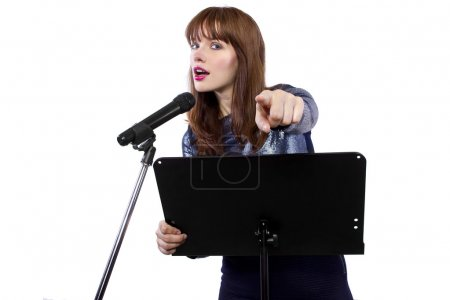 Caucasian girl speaking into a microphone and poin...