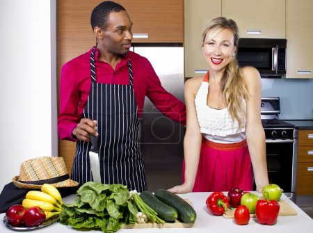 Photo for Sweet helpful boyfriend cooking for girlfriend at home - Royalty Free Image