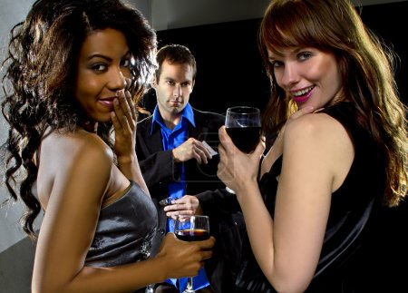 Women seducing man at bar