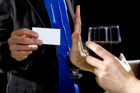 Businessman handing over businesscard to female