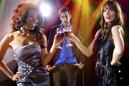 Women seducing man at bar