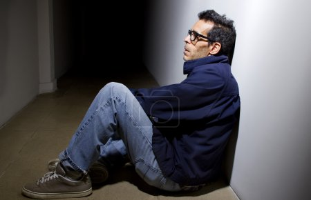 Photo for Depressed man who lost faith sitting alone in dark hallway - Royalty Free Image