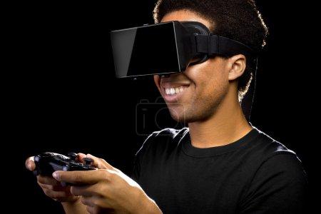 Photo pour Casque de réalité virtuelle sur un mâle noir avec le contrôleur de jeu vidéo - image libre de droit
