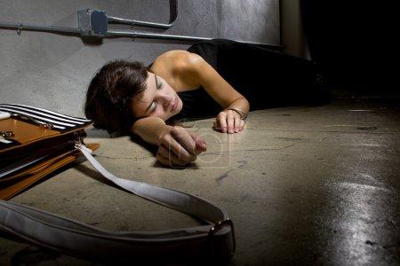 Female crime victim lying on the street floor