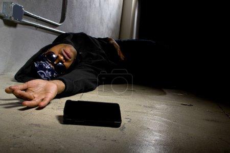 Photo pour Gangster agressé, demander une aide ou une urgence médicale avec un téléphone portable - image libre de droit
