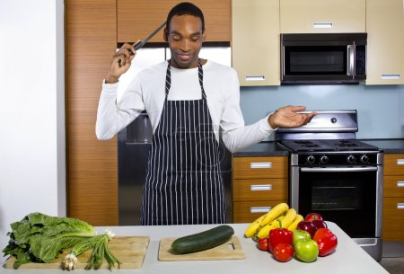 Photo for Black man learning how to cook in a domestic kitchen with fruits and vegetables - Royalty Free Image