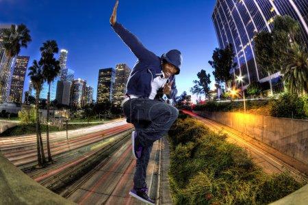 Photo pour Jeune homme noir portant un sweat à capuche bleu sautant à Los Angeles - image libre de droit