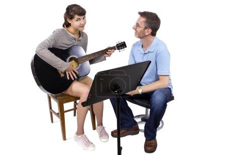 teacher tutoring female play guitar
