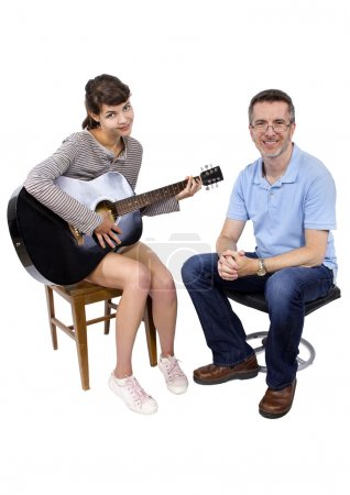 Photo for Music teacher tutoring young female student how to play guitar - Royalty Free Image
