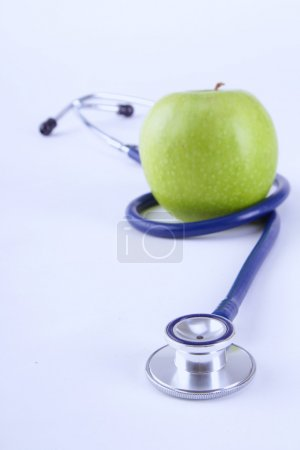 Medical stethoscope and apple isolated on white background