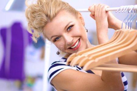 Photo pour Belle jeune styliste près de rack avec cintres - image libre de droit