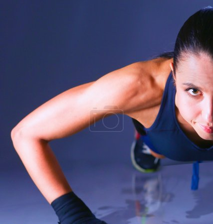 Young woman doing push ups on a mat