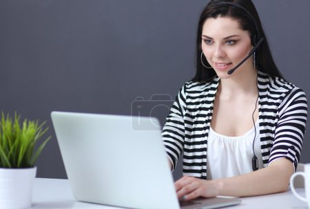Beautiful business woman working at her desk with headset and laptop