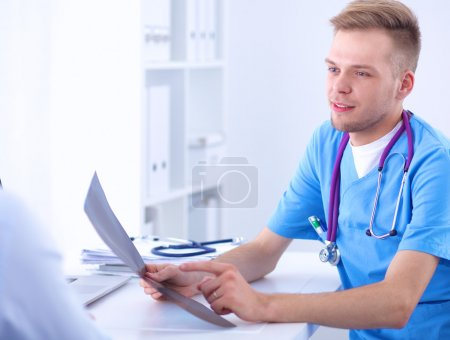 Portrait of a smiling male doctor with laptop sitting at desk in medical office