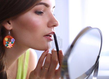 Junge schöne Frau schminkt sich in Spiegelnähe