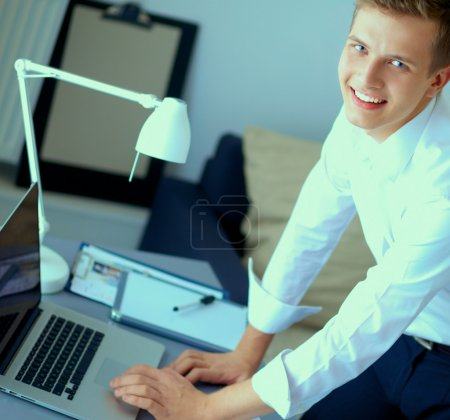 Young businessman working in office, sitting near desk