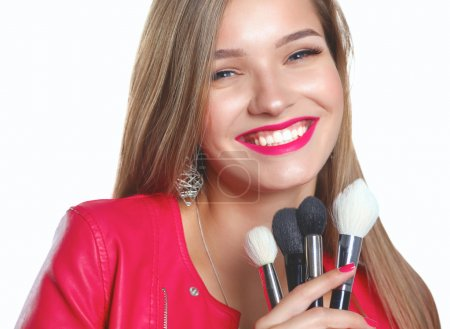 Young beautiful woman holds in hand brush for makeup