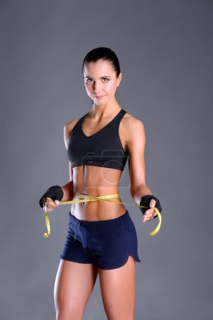 Fitness womans beautiful body with measure tape