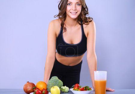 Photo for Young and beautiful woman standing near desk with vegetables. - Royalty Free Image