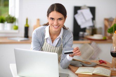 Photo pour Femme, achats en ligne en utilisant l'ordinateur et la carte de crédit en cuisine - image libre de droit