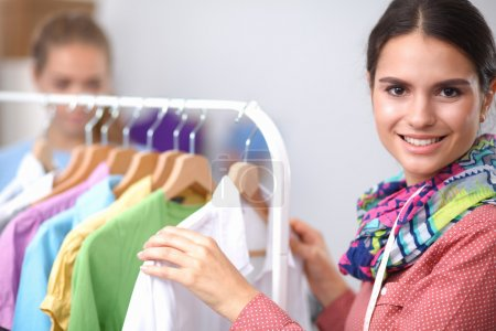 Photo for Beautiful young stylist near rack with hangers, isolated - Royalty Free Image