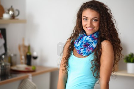 young woman standing in her kitchen