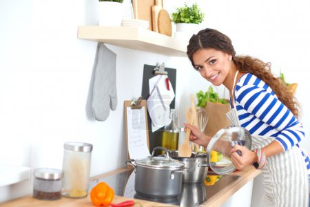 Photo for Young woman in the kitchen  preparing a food, isolated - Royalty Free Image