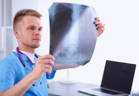 Portrait of a male doctor with x-ray picture spine in the medical office