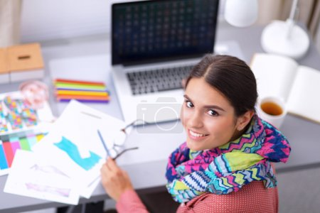 Photo for Young female fashion designer working at office desk, drawing while talking on mobile - Royalty Free Image