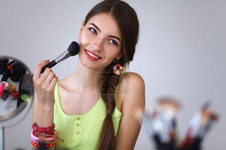 junge schöne Frau schminkt sich in der Nähe des Spiegels und sitzt am Schreibtisch