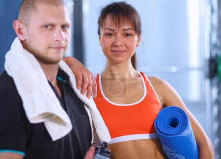 Young man and woman relaxing in sports outfits at the gym