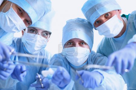 Below view of surgeons holding medical instruments in hands