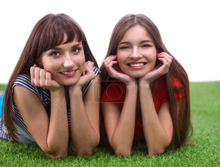Photo pour Deux jeunes femmes allongées sur l'herbe verte - image libre de droit