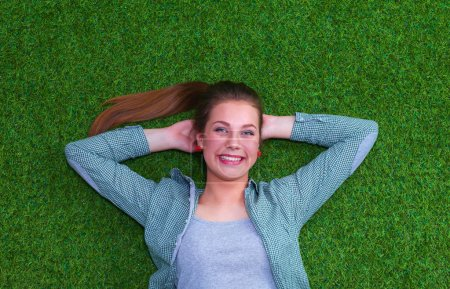 Relaxed woman  lying on the grass with hands on head