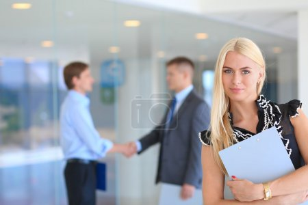 Portrait of a beautiful office worker standing in an office with businesspeople shaking hands in the background