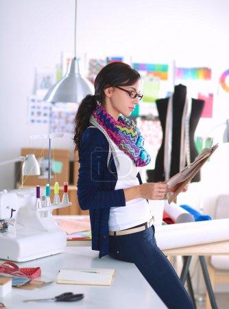 Beautiful fashion designer standing with folder in studio
