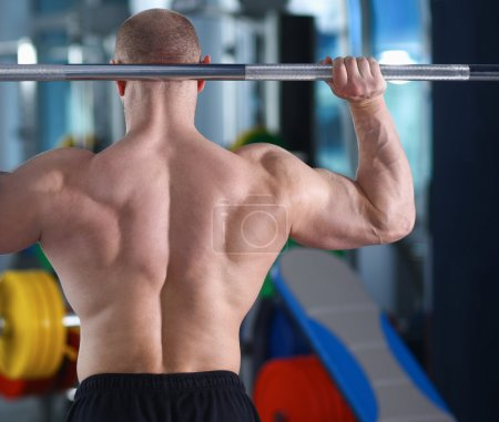 Bodybuilder with barbell in gym