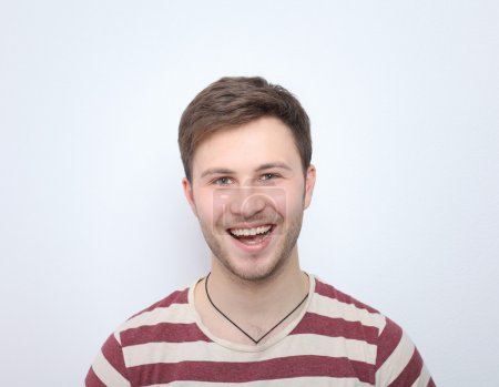 Portrait of young man smiling isolated on gray background
