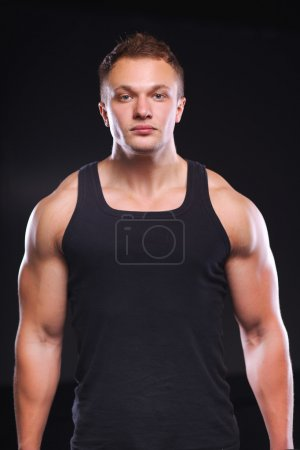 Healthy muscular young man. Isolated on black