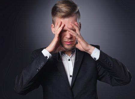 Executive man having head ache isolated on gray  background