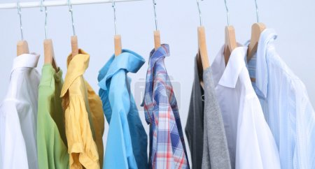 Photo for Clothes hang on a shelf in a designer clothes store - Royalty Free Image