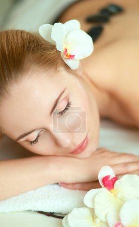 Photo pour Belle jeune femme se faire masser spa, couché sur le salon - image libre de droit