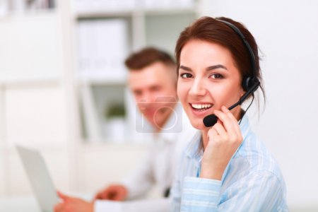 Photo for Portrait of beautiful business woman in headphones smiling with colleagues in background - Royalty Free Image
