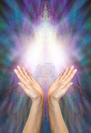 Photo pour Une paire de mains féminines atteignant vers une forme de lumière Angélique belle sur un multi couleur fond bleu et violet avec beaucoup d'espace de copie - image libre de droit