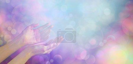 Photo pour Mains de guérison féminines doucement taillées face vers le haut vers une orbe lumineuse bleue éthérée sur un fond bokeh multicolore muet avec beaucoup d'espace de copie - image libre de droit